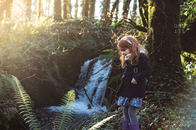 Red hair girl in rain boots standing by a waterfall in a forest