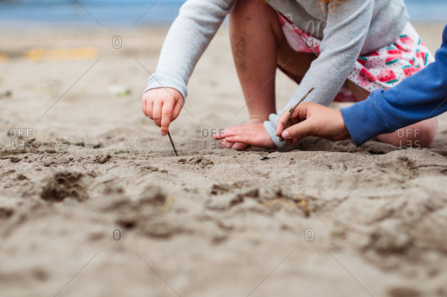 Close up of children's hands drawing with sticks on sand on a beach