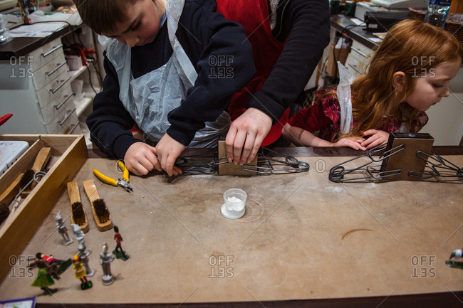 Children working with clamps with rubber molds for casting lead toy soldiers
