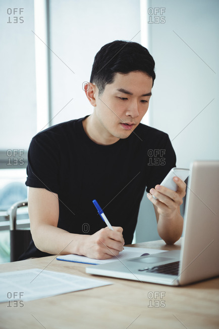 Business executive writing on diary while using mobile phone