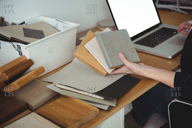 Business executive holding stone slabs and using laptop