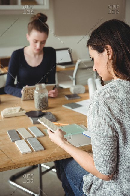 Business executive looking at stone slab while colleague using digital tablet