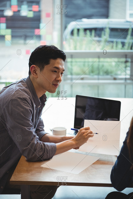 Business executives discussing over document