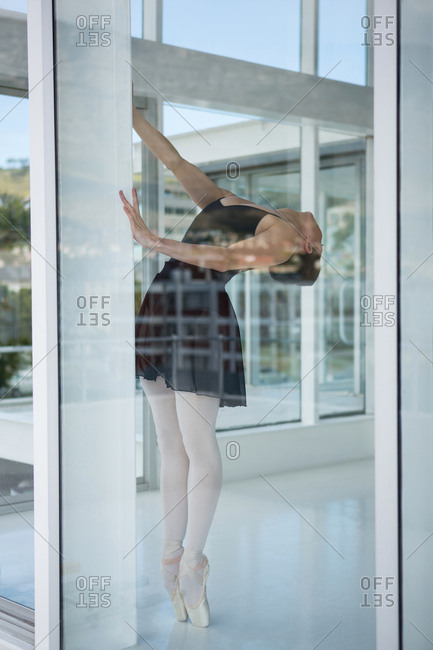 Ballerina practicing ballet dance near window