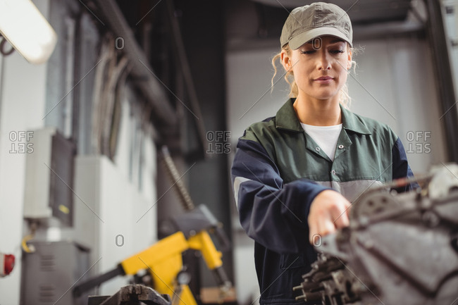 Female mechanic checking a car parts