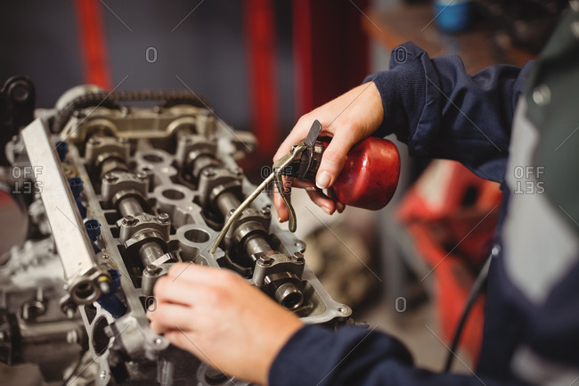 Mid-section of female mechanic oiling car parts