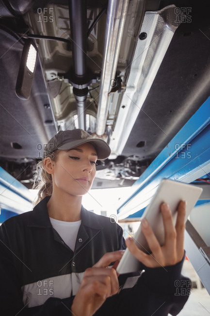 Female mechanic using digital tablet under a car