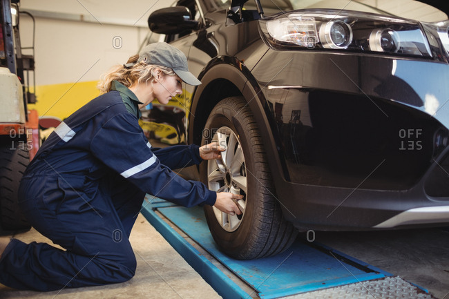 Female mechanic examining a car wheel