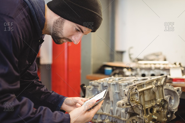 Mechanic using digital tablet on car parts