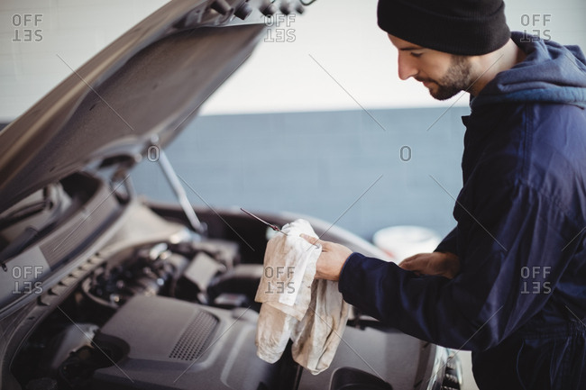 Hand of mechanic servicing car with a tool