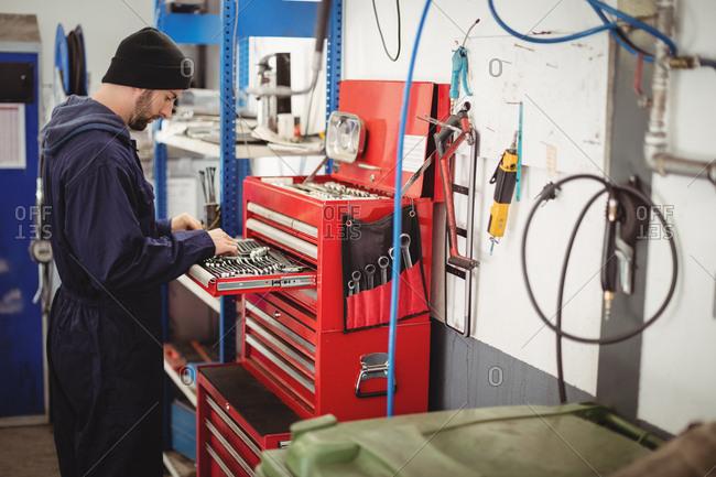 Mechanic arranging tools in toolkit