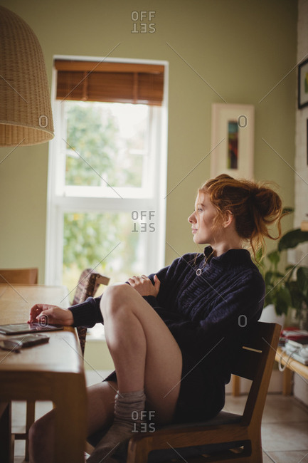 Thoughtful woman sitting at dining table