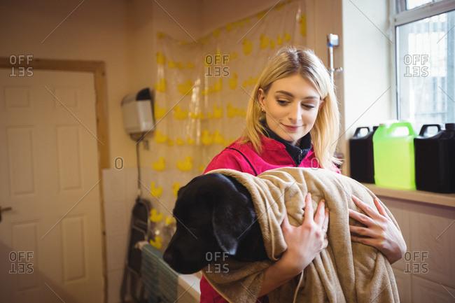 Woman holding dog in bath towel