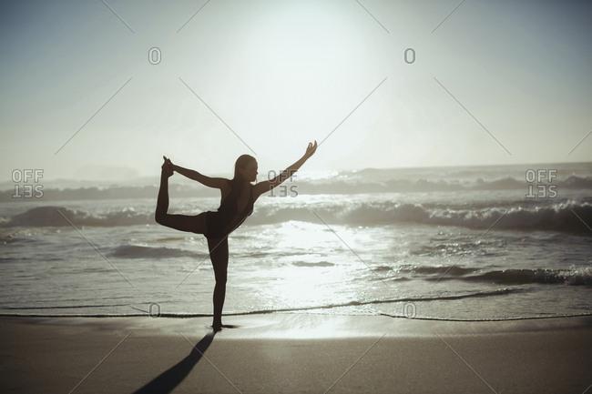 Woman performing yoga on beach