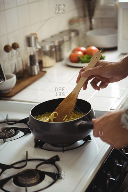 Hands of man preparing noodles in kitchen