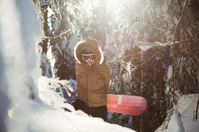 Woman with snowboard walking on snowy mountain