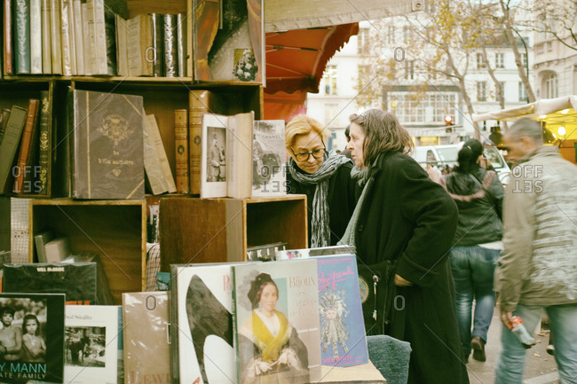 Marais, Paris - November 28, 2014: Customers browsing books at an open air flea market stall