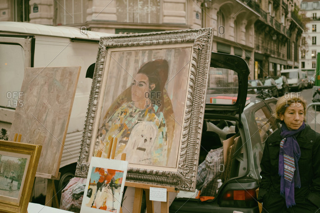 Marais, Paris - November 28, 2014: Woman selling paintings and other items at an open air flea market