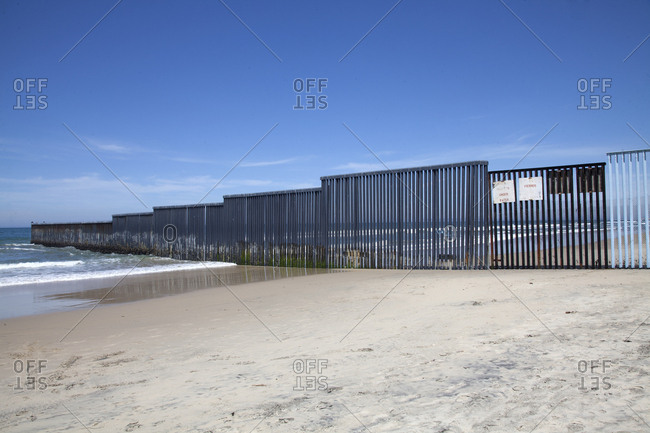 Mexican border wall on a beach