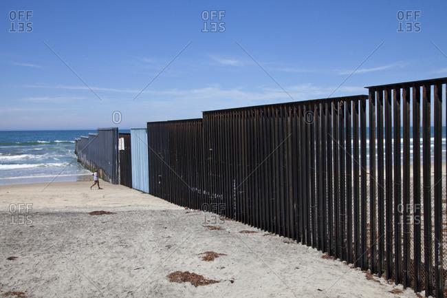 Tijuana, Mexico - October 9, 2015: Person by coastal Mexican border wall