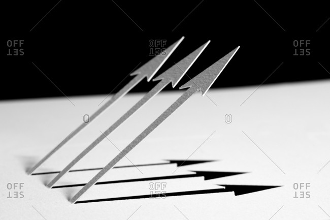 Close-up of three white paper arrows and their shadow