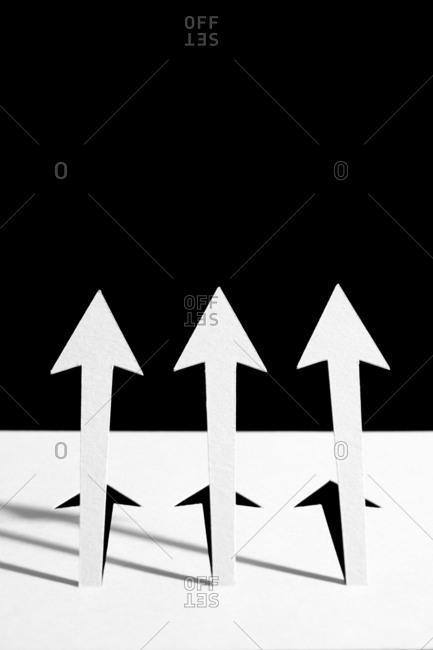 Three large white arrows pointing upwards