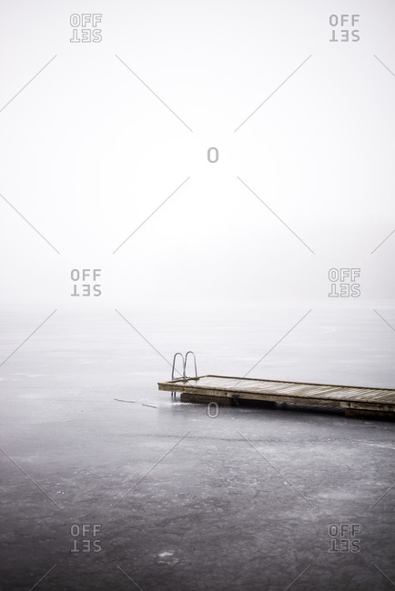 Wooden dock at a frozen lake