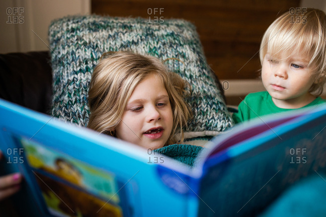 Two young children reading a book out loud