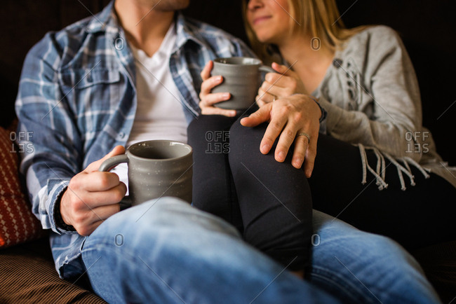 Couple snuggling on couch with coffee