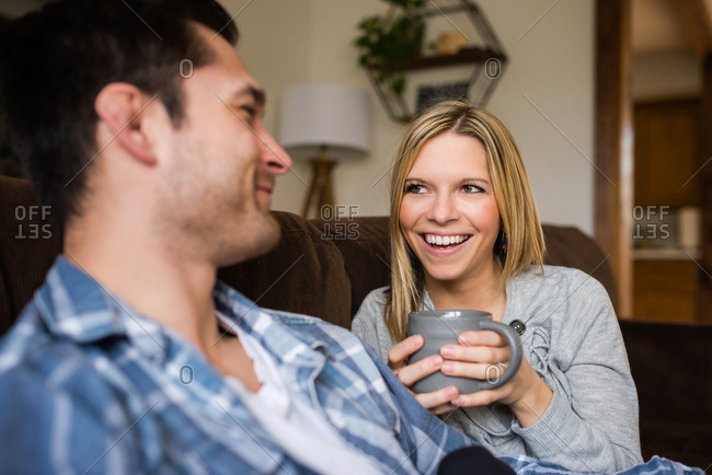 Woman on couch laughing with man