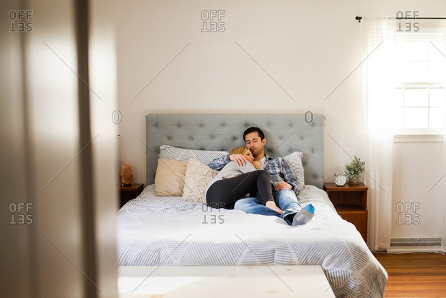 Couple snuggling on their bed