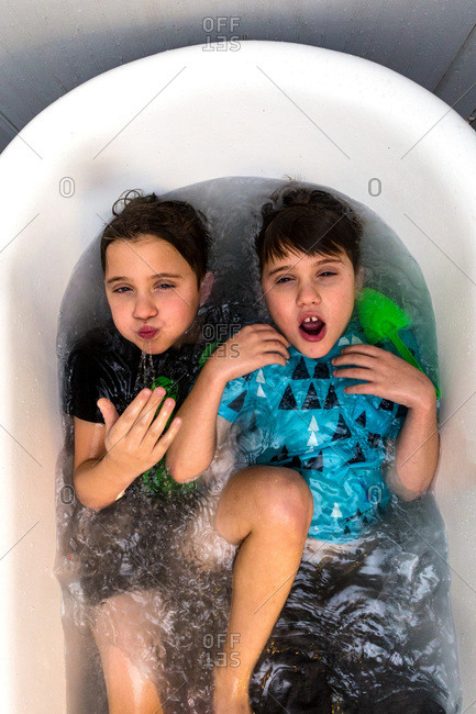 Twin Caucasian Brothers Play in Their Water Filled Bathtub Together With Their Clothes On
