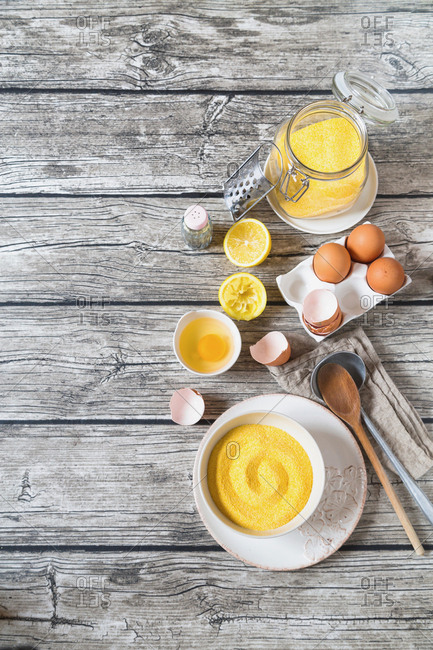 Cornmeal with eggs and lemon on rustic wooden table
