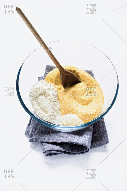 Cornmeal and flour in bowl on white background