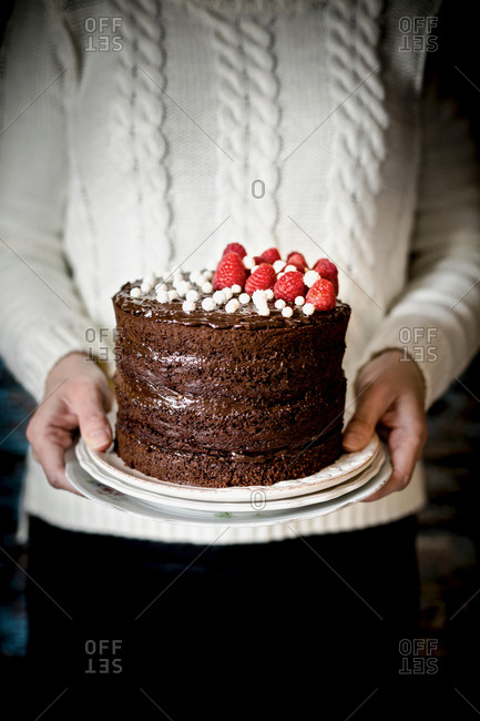 Person holding a chocolate cake topped with raspberries
