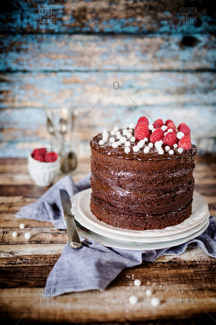Still life of a chocolate cake with raspberries on rustic wooden background