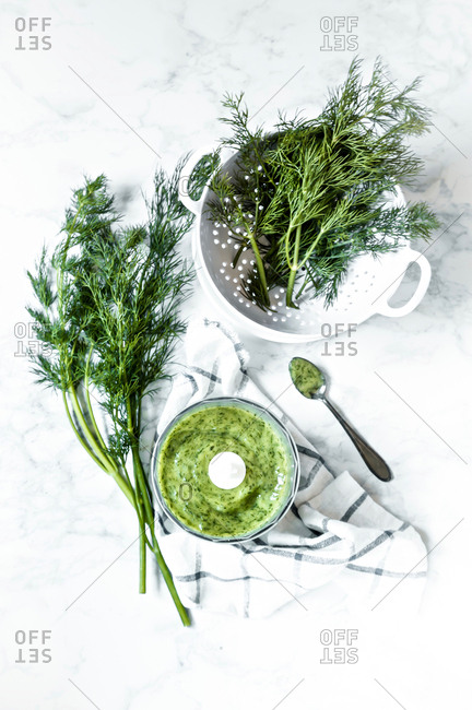 Fresh dill in colander and food processor for dill sauce