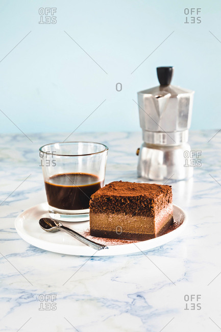 Glass of espresso with square of chocolate cake