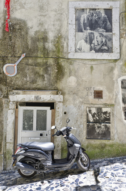 Lisbon, Portugal - June 1, 2014: Scooter parked on uphill street next to building with posters in the windows
