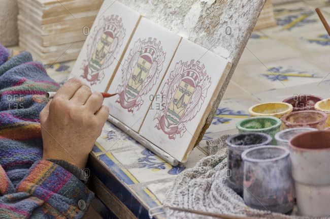 Lisbon, Portugal - March 18, 2014: Woman painting on tiles in factory