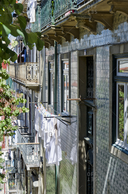 Tiled exterior of building with laundry hanging to dry outside in Lisbon, Portugal