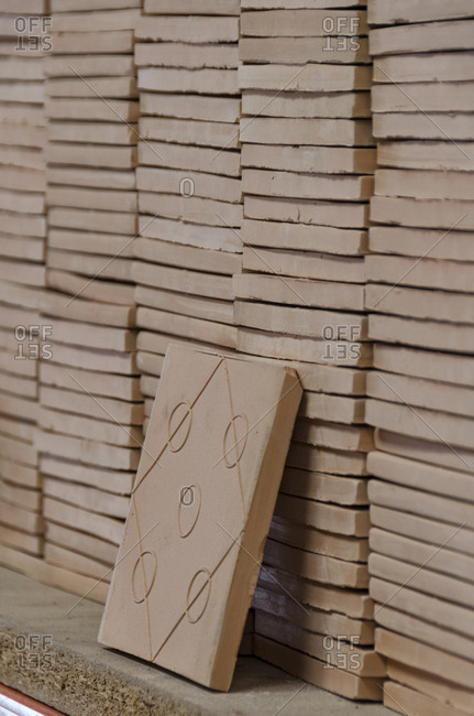 Stacks of square ceramic tiles in factory
