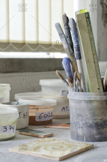 Numbered tubs and paintbrushes in tile factory
