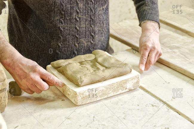 Person filling tile mold with ceramic