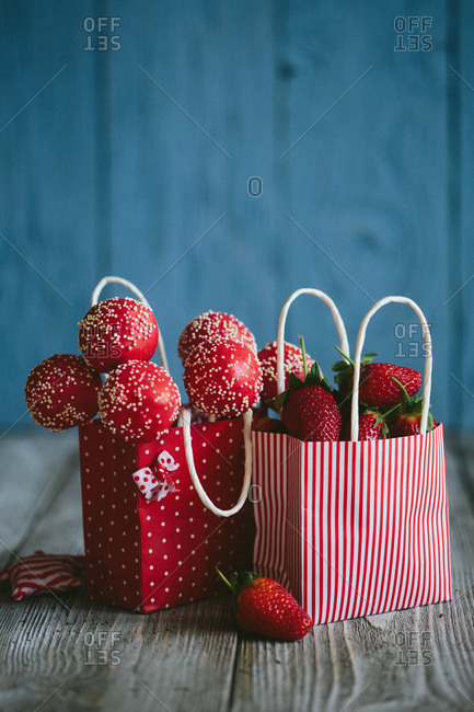 Red cake pops in bag with bag of strawberries