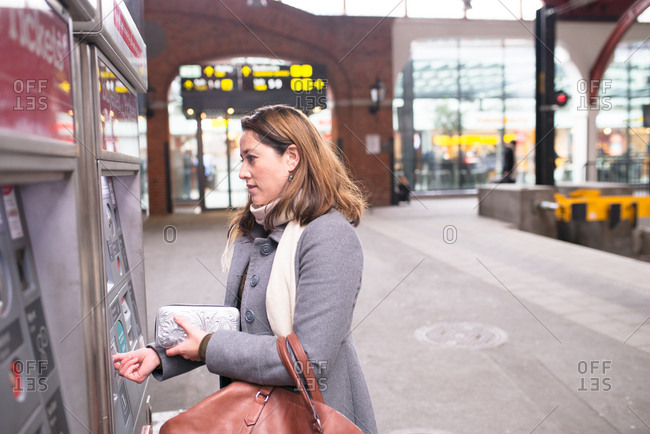 Woman buying train ticket at machine