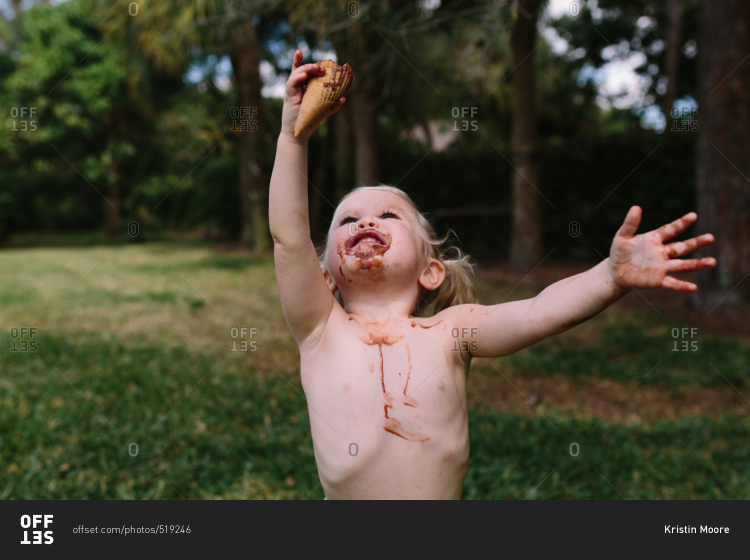 Cute toddler girl with melting ice cream cone in backyard