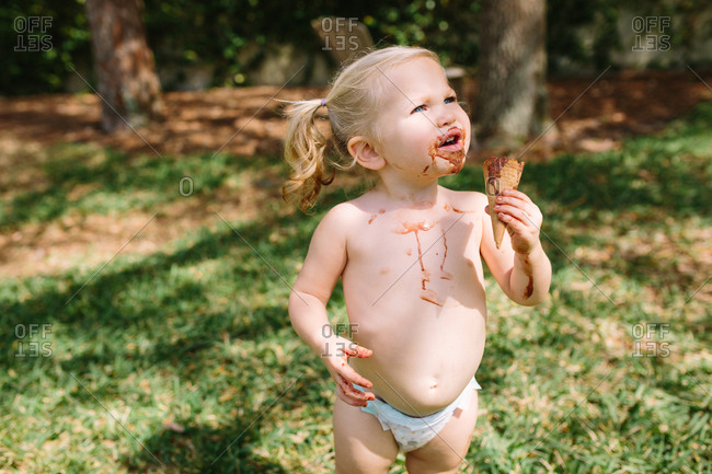 Cute toddler girl with melting chocolate ice cream cone