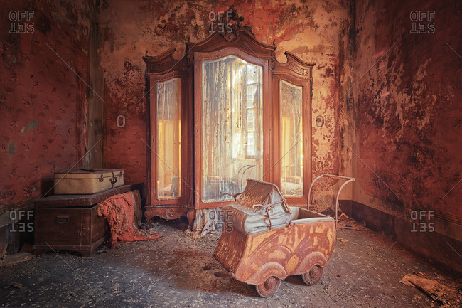 Baby carriage, mirror, and suitcase in room in abandoned villa