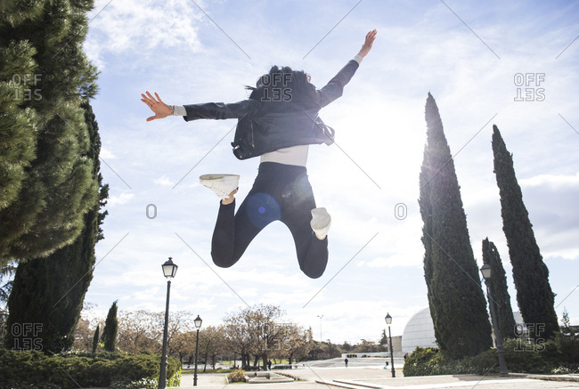Back view of young woman jumping in the air at backlight